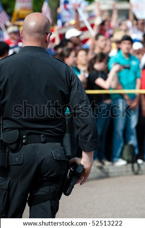A bald policeman in a black uniform confronts crowds of protesters carrying signs and banners.