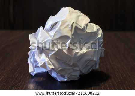 A ball of crumpled paper on a dark brown table
