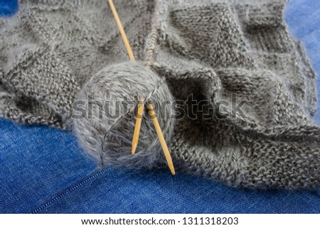 A ball of gray mohair yarn, knitted scarf and bamboo knitting needles on blue background