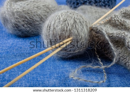 A ball of gray mohair yarn, knitted scarf and bamboo knitting needles on blue background, close-up