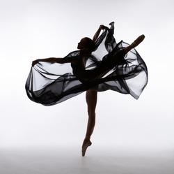 A ballerina dances with a black cloth. Color photo.