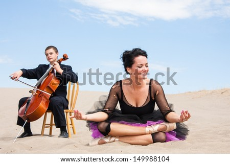 A ballerina in a relaxing yoga pose in the desert-closes her eyes.  a Cellist plays  a dreamlike solo in the background.