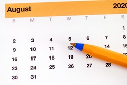 A ballpoint pen lying on a calendar that is showing august month. Close up.