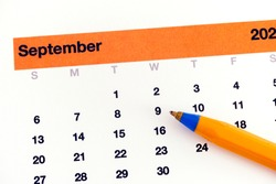 A ballpoint pen lying on a calendar that is showing September month. Close up.