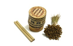 A bamboo box or bamboo rice box surrounded by a small bouquet of dry Chris indica and two bamboo tubes