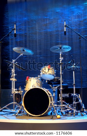 A band's percussion kit standing empty against a background of blue falling water and rocks. Space for text on the drum, or on the background.