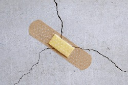 A bandage is stuck to a crack in the concrete wall.