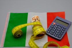 A banknote wrapped in a centimeter by a seamstress, next to a calculator, on top of an Italian flag. Concept of close on pensions