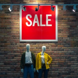 A banner in a clothing store informing about the ongoing sale, hanging on a brick wall and illuminated by spotlights above two mannequins in clothes. Sale season.