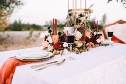 A banquet on nature, a table with a white tablecloth, vintage plates with a gold rim, wine glasses, cutlery, candles, a composition of flowers, amaryllis, roses, red dahlias.