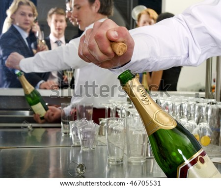 A bar man opening a bottle of champagne behind a bar, with several people reflected in the mirror behind him