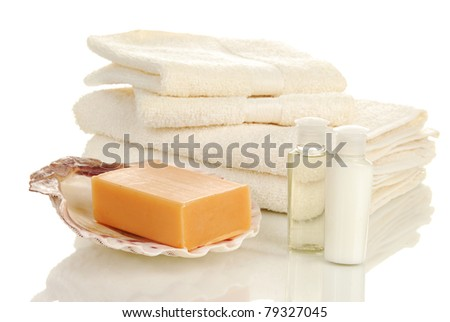 A bar of natural soap, with hand towels and wash cloths, shampoo and body lotion