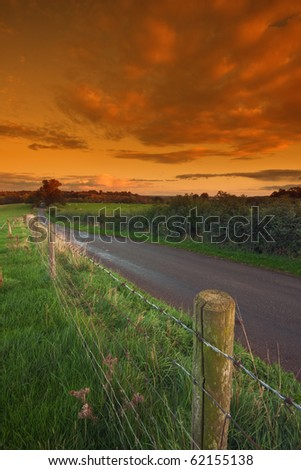 A barbed-wire fence running alongside a typical country road in rural Warwickshire, England, with sunset sky in the background.