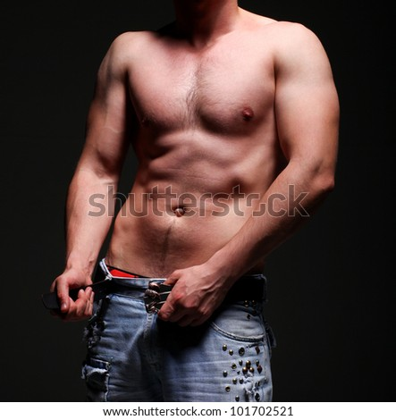 A bare-chested handsome young man in jeans showing his abs