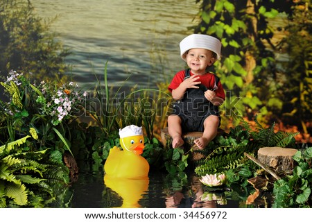 A barefoot baby boy happily playing by the water's edge with a rubber duck -- both in sailor's hats.