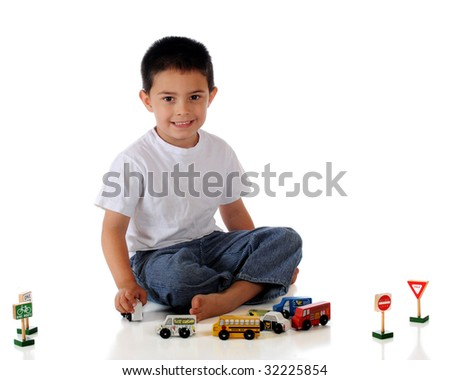 A barefoot kindergarten boy playing with an assortment of cars, trucks and traffic signs.  Isolated on white.