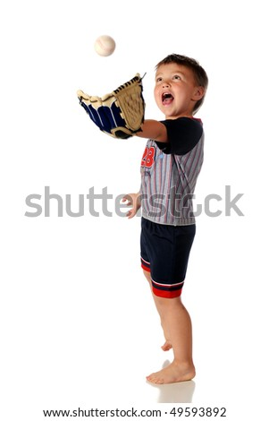 A barefoot, open-mouthed preschooler in a baseball outfit catching a ball with his mitt.  Isolated on white.  Ball has motion blur.
