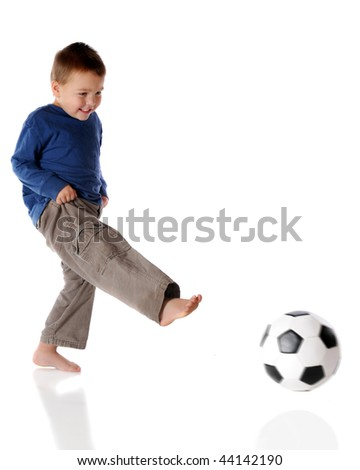A barefoot preschooler kicking a soccer ball.  Isolated on white.  (Ball has motion blur.)