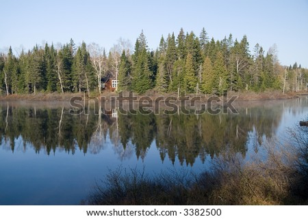 A barely visible fishing cabin on the Mastigouche Nature Reserve in Quebec. - stock photo