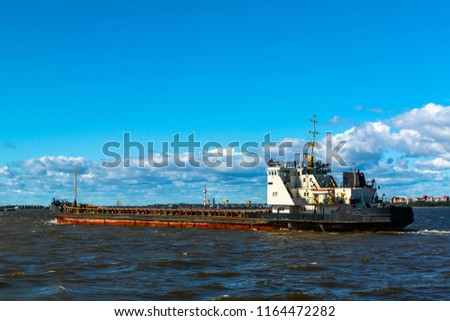 A barge floating along the sea along the shore. The sea barge is transporting goods of the appropriate destination. The sea is calm. The weather is sunny.