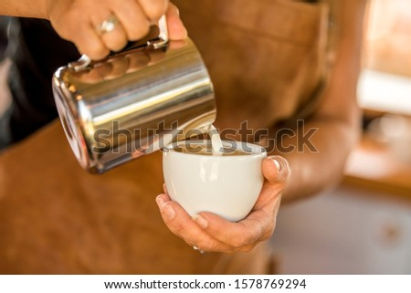 A barista pouring foam milk to a fresh shot of espresso. Just making a fresh and delicious cup of cappuccino. An authentic barista doing her job in a room filled with the aroma of freshly ground beans