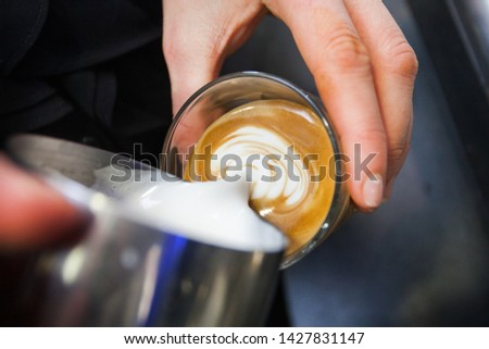 A barista pouring hot milk from a metal jug into a freshly poured espresso #1427831147