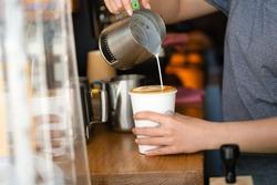 a barista pouring milk making a take away coffee