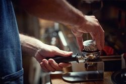 A barman behind the bar is preparing an aromatic and fragrant espresso beverage. Coffee, beverage, bar