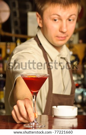 A barman holding the glass with cocktail - indoors