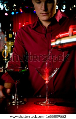 A barman mixing cocktails in a bar
