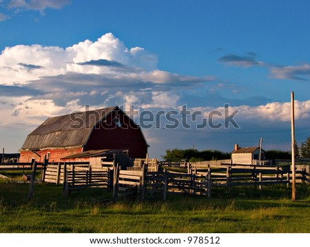 A barn and farmyard shot against a cloudy sky.