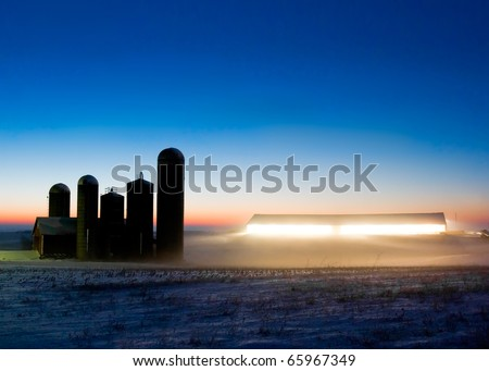 A barn and silos on a dairy farm in the middle of winter at twilight.