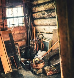 A barn in an old wooden log house full of antique agricultural rustic items made of metal, wood. Openwork forged lattice on a small window. The cracks are plugged with moss. Warm colors, wide angle.