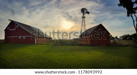 A barnyard with windmill set on the South Dakota plains at Sunset.