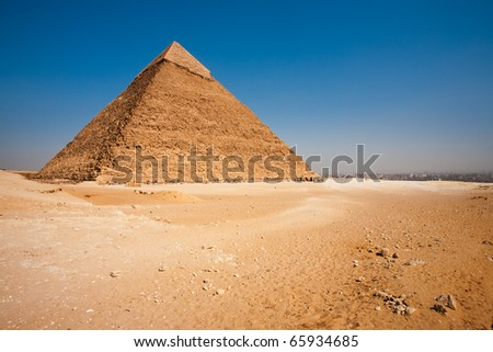 A barren desert and the rear of the Pyramid of Khafre looking onto a view of Cairo, Egypt.