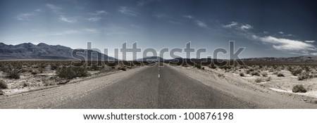 A barren stretch of asphalt extends into the vast wilderness of Death Valley National Park.