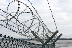 A barrier of rolled up vicious razor wire on top of a wire fence leads out towards a beach near Thorney Island British army base. The sky is grey and overcast giving a grim depressing view.