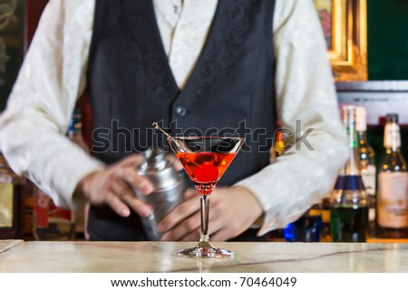 A bartender makes a cocktail over the marble bar counter