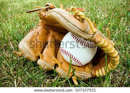 a baseball and an old baseball glove lying on the a baseball field.