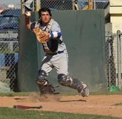 A baseball catcher throws to first base to check the runner.