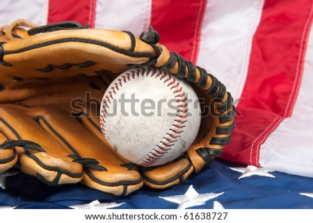 A baseball glove and baseball on an American flag.