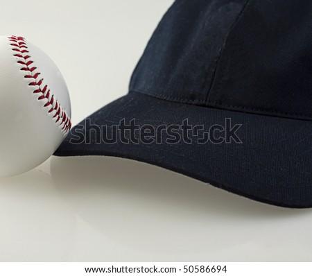 A baseball near a baseball hat