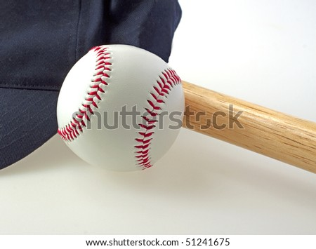 A baseball near a bat and a blue hat