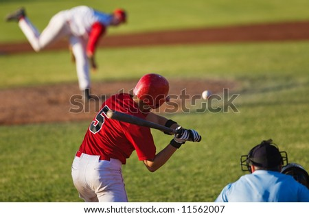 A baseball player ready to swing at the ball(focus on batter)