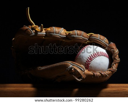 A baseball sits in a mitt on a wood bench set against a dark background.