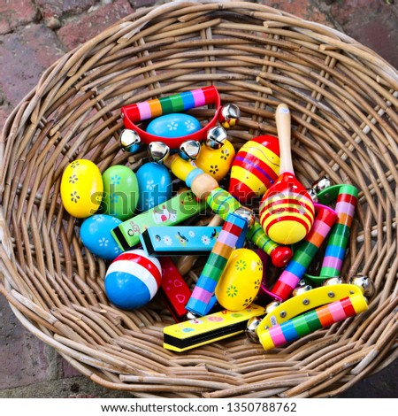 A basket filled with colorful musical percussion instruments. Music and childhood concept image.