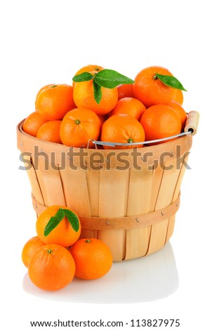 A basket full of Clementine Mandarin Oranges. Vertical format over a white background with reflection.