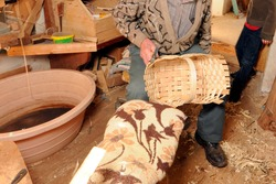 a basket maker weaves a basket, crafting and producing with wood