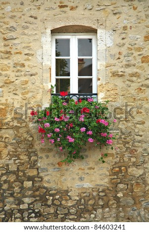 A basket of bright pink and red flowers hangs on the window of a home in an ancient building in France, surrounded by beautiful patterns in the stone wall.