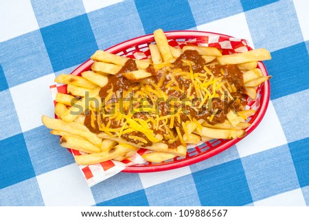 A basket of chili cheese fries covered in hot chili and melted cheddar cheese.
